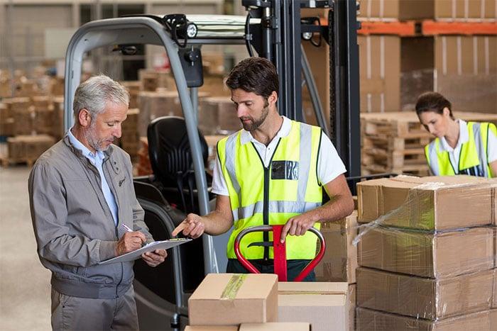 Older supervisor instructing a forklift operator in a warehouse