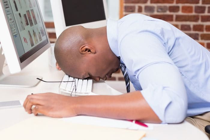 Young business owner hanging his head in defeat after working on his business website